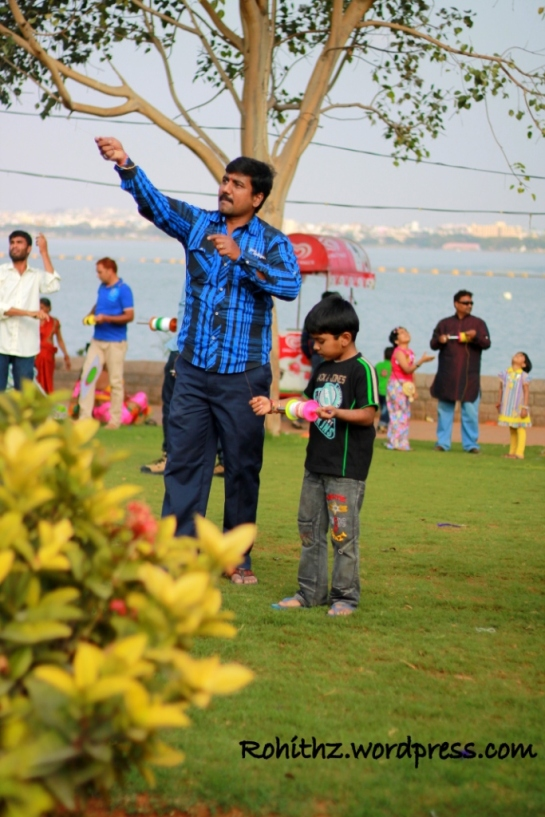 An enthusiastic son helping his dad to fliying kites