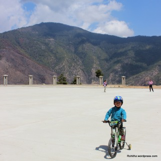 Little boy cycling around Buddha statue..